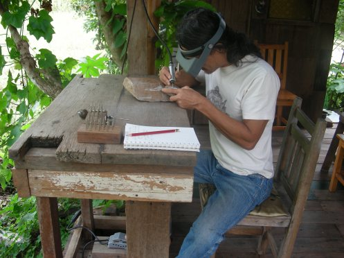 Neng  at  his Workbench on Deck of his Studio in ChaingMai, Thailand